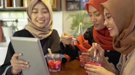 lebaran : Veiled young women relaxing with chatting and joking using digital tablet Stock Footage