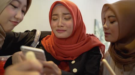 lebaran : Hijab women and friends sad when reading bad news Stock Footage