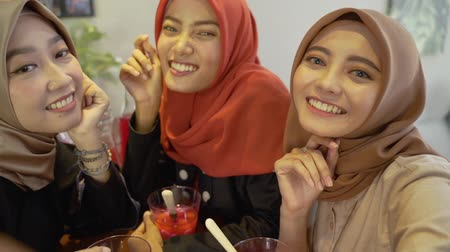 lebaran : Veiled young women relaxing using smartphone for selfie Stock Footage