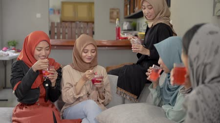 malaya : Veiled young women enjoy together a fruits cocktail