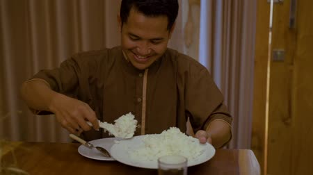 indonesian : male eating rice while having dinner