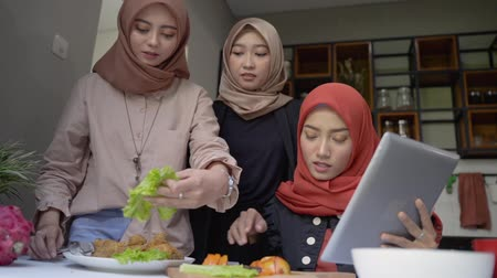 lebaran : hijab woman and friends plating a cuisine in the kitchen Stock Footage