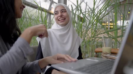 asian and indian ethnicities : muslim woman and friend discussing with laptop