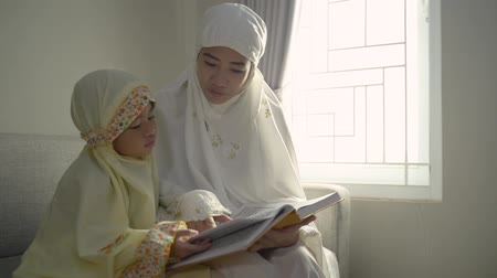 holy book : muslim parent and daughter reading quran