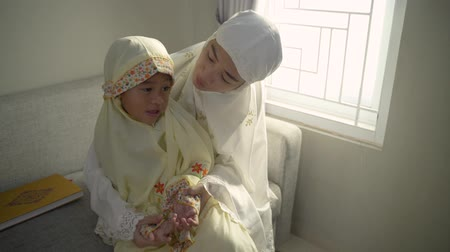 Аллах : mother teach her daughter to pray with her hand open palm