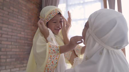 malajské : mother help her young daughter to put the scarf on Dostupné videozáznamy