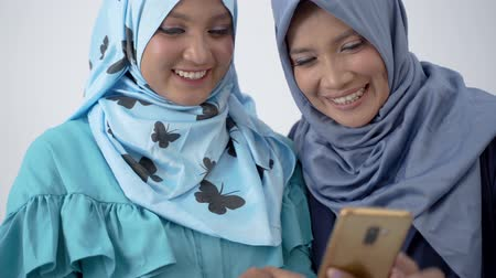 lebaran : Portrait of veiled young woman showing a smartphone to her mother while laughing happily