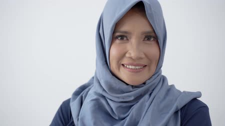 lebaran : Close up of old hijab woman with crossed hands and smile look at camera Stock Footage