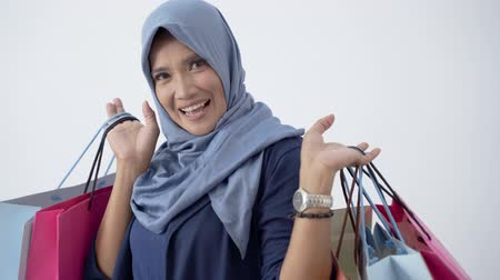 lebaran : Asian older veiled woman happy carrying a lot of shopping bags