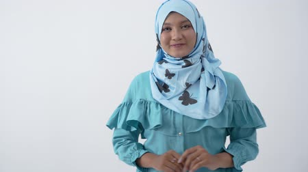 lebaran : Beautiful veiled woman standing with hands gesture holding something Stock Footage