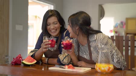 lebaran : Portrait of two women slice a dragon fruit