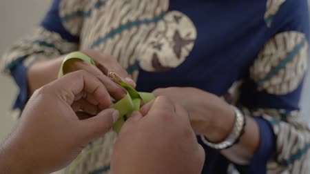 sarıcı : mother and daughter learning how to make a woven wrapper of ketupat