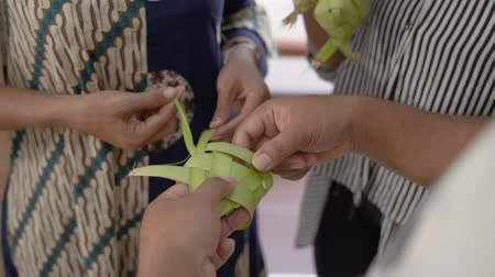 sarıcı : mother and daughter make a woven wrapper of ketupat