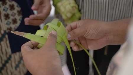 lebaran : mother and daughter make a woven wrapper of ketupat
