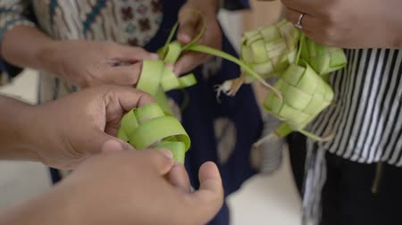 rice cake : mother and daughter learning how to make a woven wrapper of ketupat