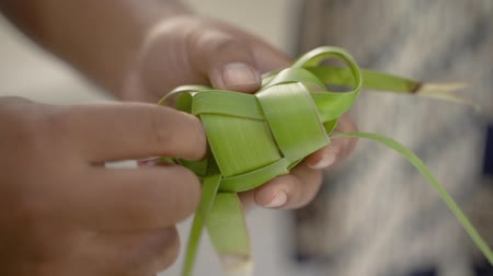編まれた : Close up of hands man make traditional ketupat food 動画素材