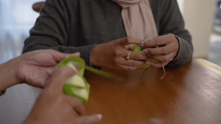 rice cake : Two veiled woman make a woven wrapper of ketupat