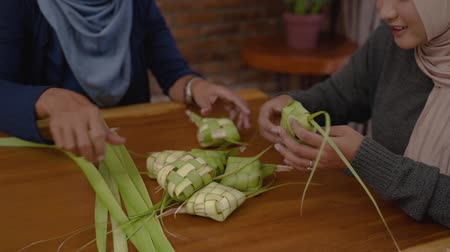 rice cake : women make traditional ketupat food for Eid celebrations at home Stock Footage