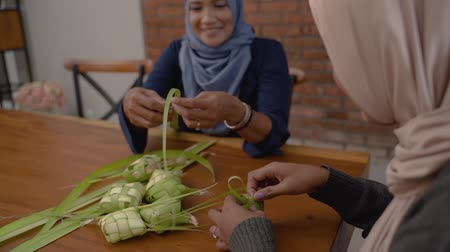 lebaran : women make traditional ketupat food for Eid celebrations at home Stock Footage