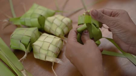 lebaran : women hands make traditional ketupat food Stock Footage