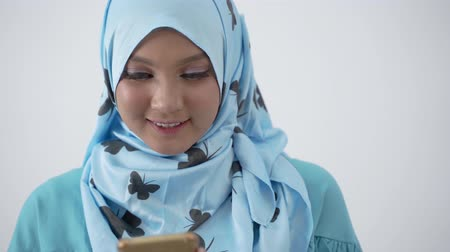 lebaran : Close up of asian veiled woman using smartphone