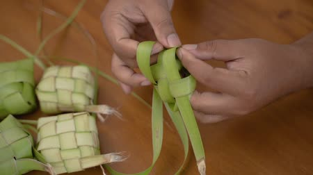 rice cake : man hands make a woven wrapper of ketupat