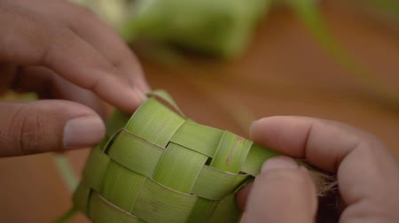 lebaran : Close up of hands man make traditional ketupat food Stock Footage