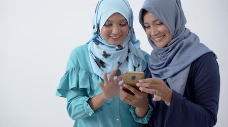 lenço : Portrait of veiled young woman showing a smartphone to her mother and together seeing it