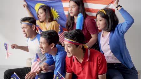 гордый : excited asian young supporter holding malaysia flag