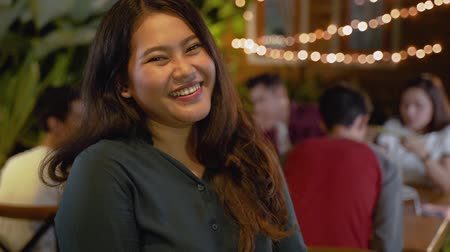 handen ineen : attractive asian woman smiling to camera while having dinner garden party