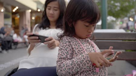 engrossed : mother and child engrossed in her smartphone Stock Footage