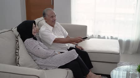 family watching tv : senior couple holding a remote to choose television channels