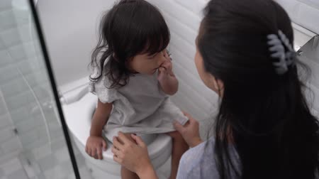 banquinho : mother help her daughter to sit on the toilet
