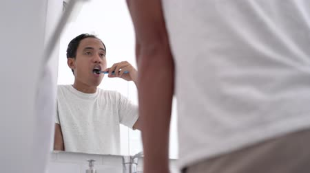 preventive : asian male brushing his teeth