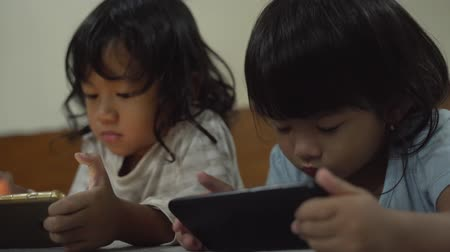 lay : two toddler using gadget at home