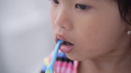 escova de dentes : asian little girl brushes her teeth alone in the bathroom