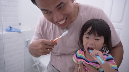 escova de dentes : father and daughter brushing teeth together
