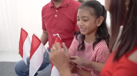 decoración vivienda : Familia indonesia sosteniendo la bandera de Indonesia sobre fondo blanco. Archivo de Video