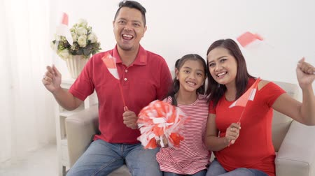 indonesian family holding indonesia flag over white background