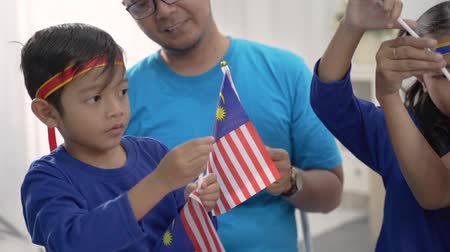 kids making malaysian flags together at home with family