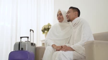 muslim couple sit wearing white traditional clothes before umrah