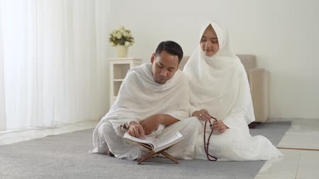 hacı : asian young couple praying with Al-Quran and prayer beads Stok Video