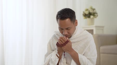 muslim asian man praying with prayer beads