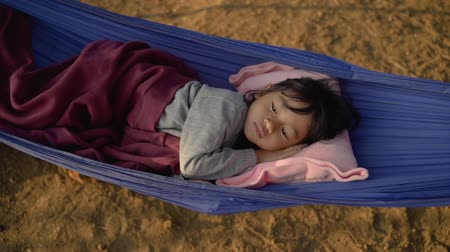 asian kid relaxing on hammock outdoor