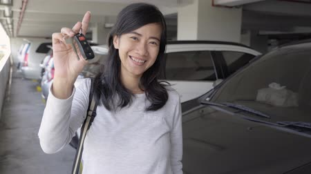 auto parking : woman shows a key that is held Stock Footage