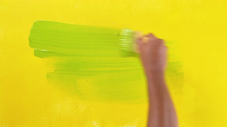 footage paints a wall with a brush to apply light green paint Wideo
