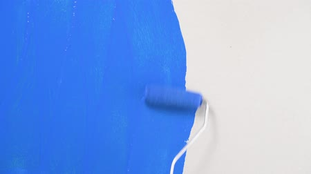 Footage roller for painting walls with blue paint on the wall