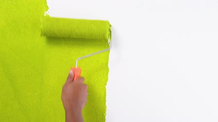 Footage hand painting a white wall with a light green paint roller
