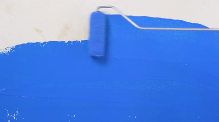 pára choque : footage paints a wall with a roller to apply blue paint