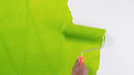 pára choque : Footage hand painting a white wall with a dark green paint roller Vídeos